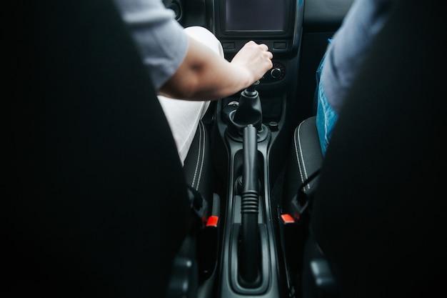 Männliche hand, die einen automatischen schalthebel in einem neuen auto zieht. schaltgetriebe. freude am autofahren. verschwommener vorderer vordergrund und fokus auf die hand des mannes. Premium Fotos