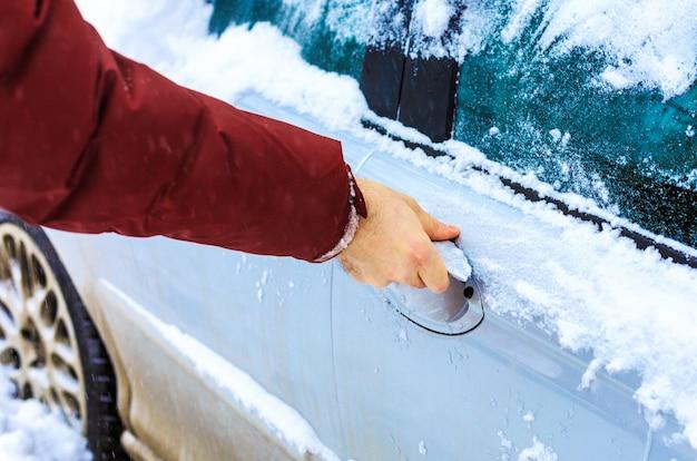 Männliche hand, die gefrorenen autoschloss entsperrt Premium Fotos