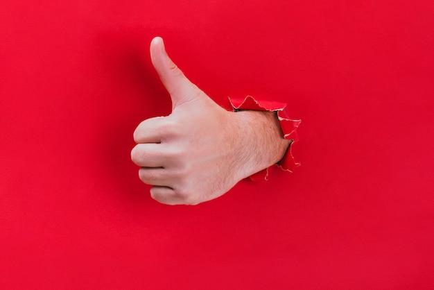 Männliche hand durchbricht das rote papier und zeigt seinen daumen. Premium Fotos