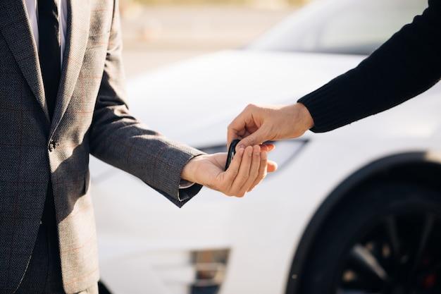 Männliche hand gibt einen autoschlüssel zu männlicher hand in der autohausnahaufnahme Premium Fotos