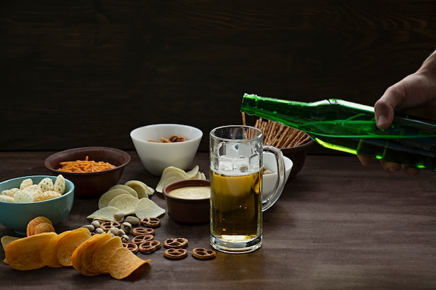 Männliche hand gießt bier. bier mit brezeln und verschiedenen imbissen. Premium Fotos