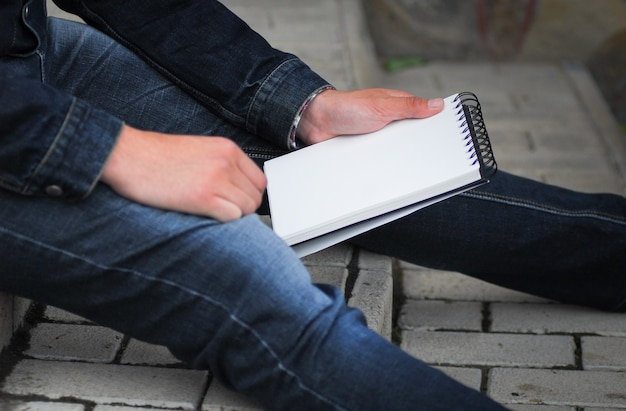 Männliche hand hält ein buch und sitzt draußen Premium Fotos