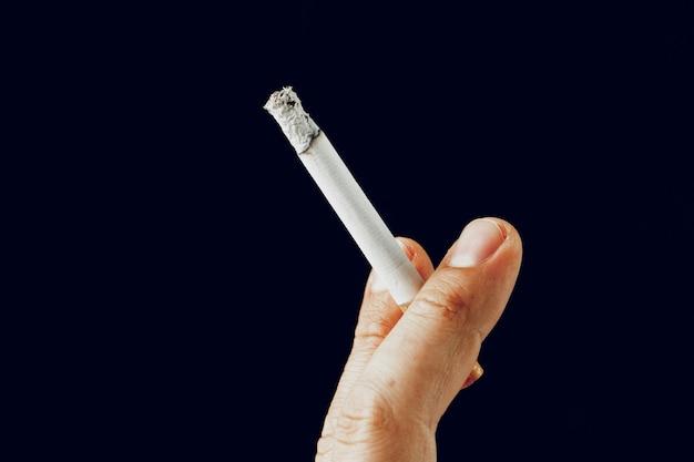 Männliche hand mit einer brennenden zigarette gegen schwarzen hintergrund Premium Fotos