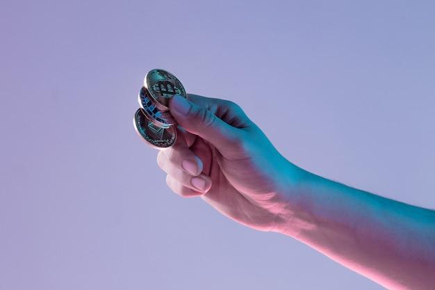Männliche hand mit goldenem bitcoin auf blauem hintergrund Kostenlose Fotos