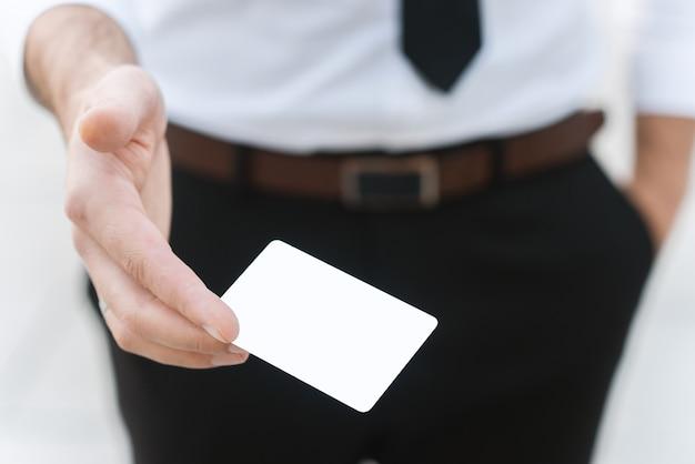 Männliche hand mit weißer leerer visitenkarte, nahaufnahmefoto mit selektivem fokus Premium Fotos