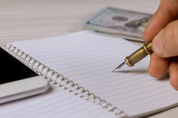 Männliche hand schreibt einen stift in notizblock die dollar, smartphone Premium Fotos