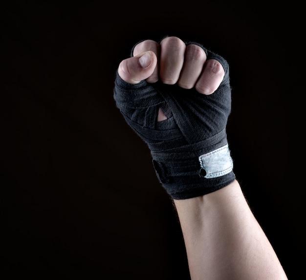 Männliche hand wird in einen schwarzen sporttextilverband eingewickelt Premium Fotos