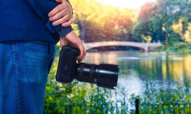 Männliche kameramannhände mit digitalkamera, nahaufnahme, grüner natur und see Premium Fotos
