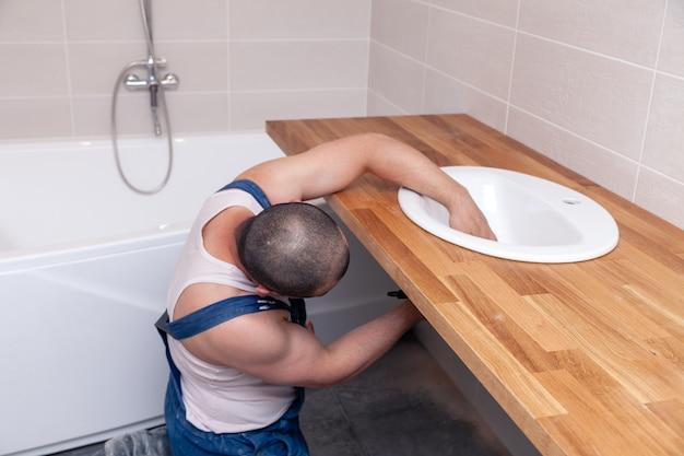 Männliche klempnerarbeitskraft der nahaufnahme in der blauen denimuniform, overall, wanne im badezimmer mit fliesenwand reparierend. professioneller sanitärreparaturservice, installation von wasserleitungen, kanalisation am mann Premium Fotos