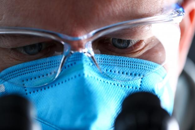 Männliche laborantenaugen, die das mikroskop trägt schutzmaske betrachten Premium Fotos