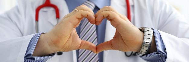 Männliche medizinarzthände, die herzform zeigen Premium Fotos