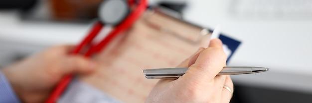 Männliche medizinarzthände, die kardiogrammkarte halten Premium Fotos