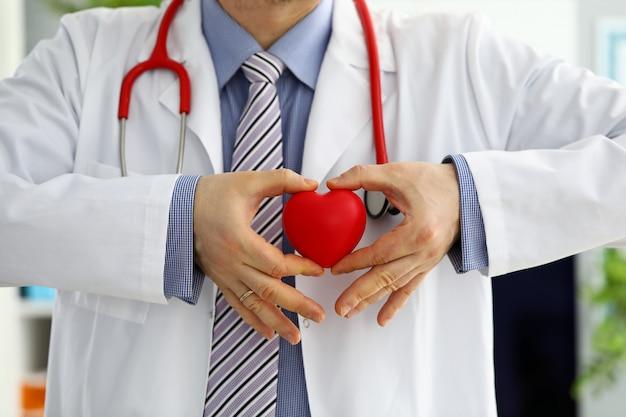 Männliche medizinarzthände, die rotes spielzeugherz halten und bedecken Premium Fotos