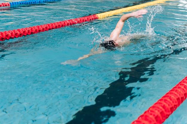 Männliche schwimmen des hohen winkels im becken Kostenlose Fotos