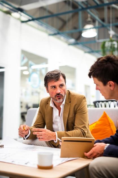 Männliche sitzung des hohen winkels im büro Kostenlose Fotos