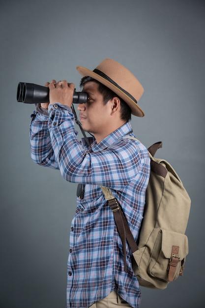 Männliche touristen, die den grauen hintergrund der ferngläser halten wandern. Kostenlose Fotos
