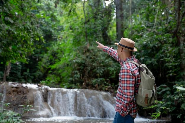 Männliche touristen sind glücklich und erfrischt am wasserfall. Kostenlose Fotos