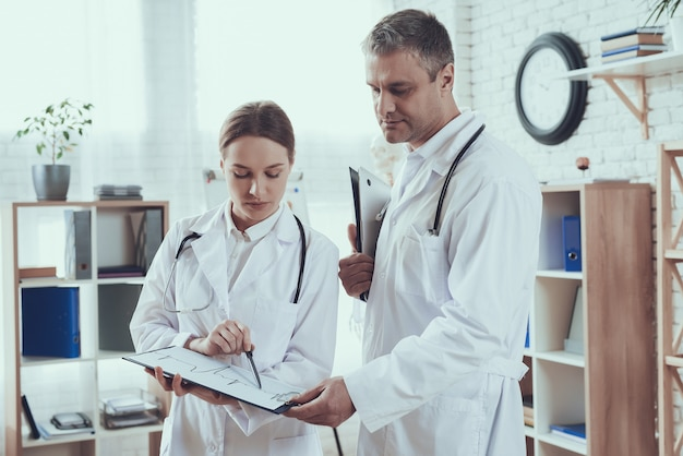 Männliche und weibliche ärzte mit stethoskopen im büro. ärzte vergleichen notizen. Premium Fotos