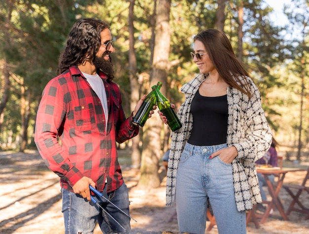 Männliche und weibliche freunde, die mit bier über dem grill rösten Kostenlose Fotos