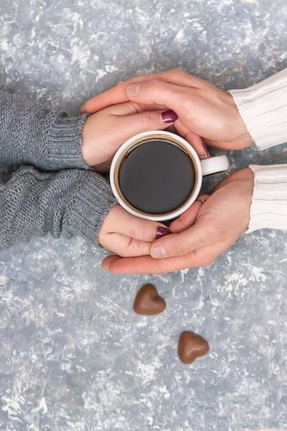 Männliche und weibliche hände, die tasse kaffees halten. selektiver fokus Premium Fotos