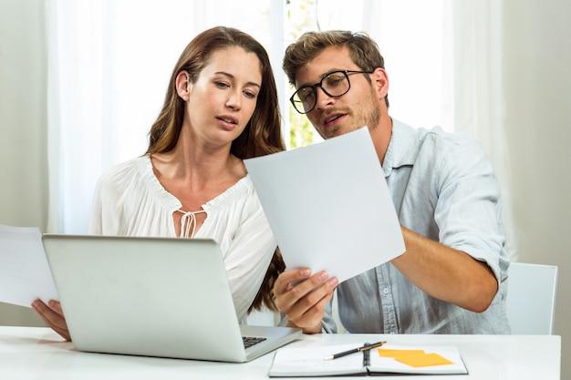 Männliche und weibliche kollegen, die dokument im büro besprechen Premium Fotos