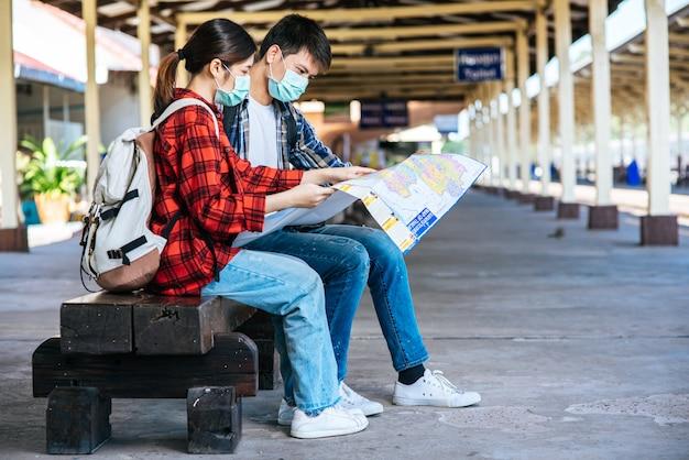 Männliche und weibliche touristen schauen auf die karte neben der eisenbahn. Kostenlose Fotos