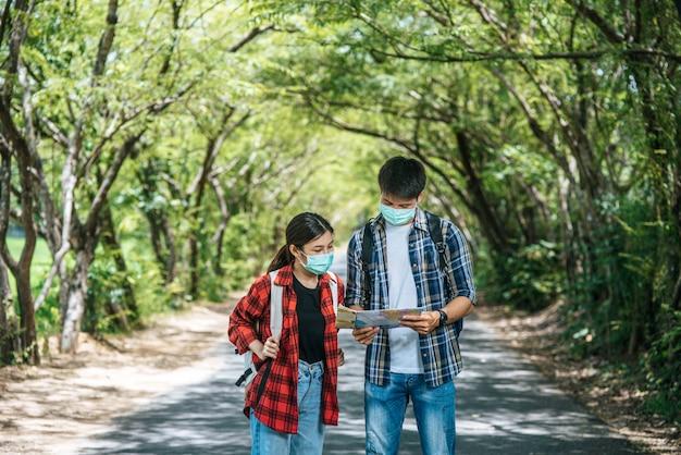 Männliche und weibliche touristen tragen medizinische masken und schauen auf die karte auf der straße. Kostenlose Fotos
