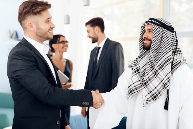 Männlicher araber und investor rütteln hände im büro. Premium Fotos