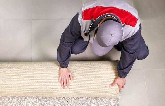 Männlicher arbeiter, der teppich auf boden zu hause abrollt, ansicht von oben Premium Fotos