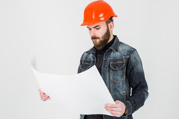Männlicher architekt, der weißen plan gegen weißen hintergrund betrachtet Kostenlose Fotos