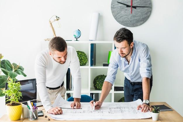 Männlicher architekt zwei, der plan im büro vorbereitet Kostenlose Fotos
