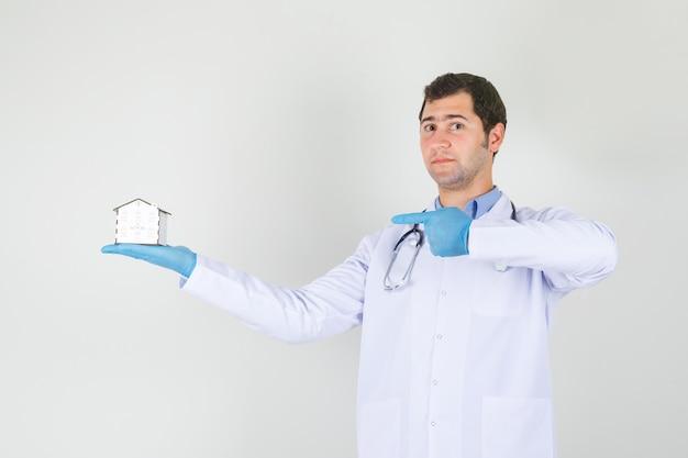 Männlicher arzt, der finger auf hausmodell im weißen kittel zeigt, handschuhe vorderansicht. Kostenlose Fotos