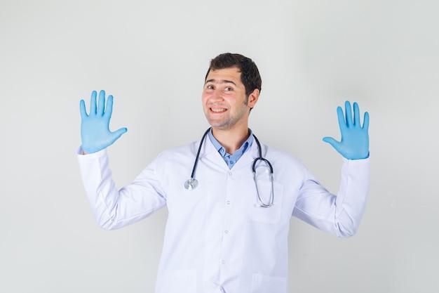 Männlicher arzt, der höflich ablehnungsgeste im weißen kittel, in den handschuhen zeigt und fröhlich aussieht Kostenlose Fotos