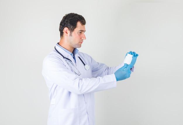 Männlicher arzt hält flasche pillen im weißen kittel, handschuhe und sieht ernst aus Kostenlose Fotos