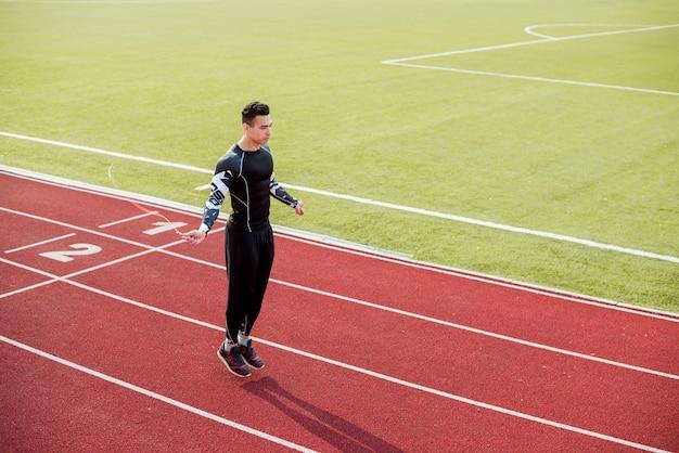 Männlicher athlet, der auf roter rennstrecke im stadion überspringt Kostenlose Fotos
