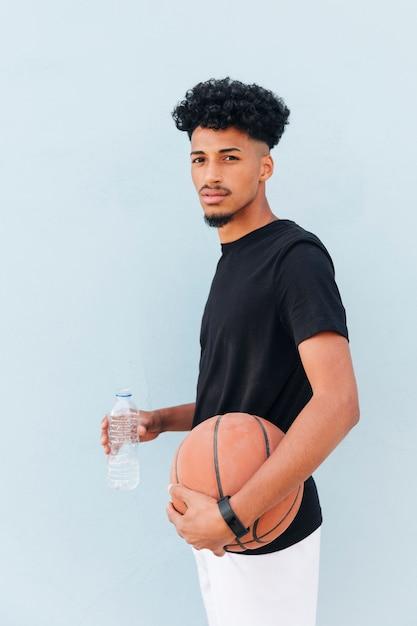Männlicher athlet, der mit basketball- und plastikflasche auf weichem blauem hintergrund steht Kostenlose Fotos