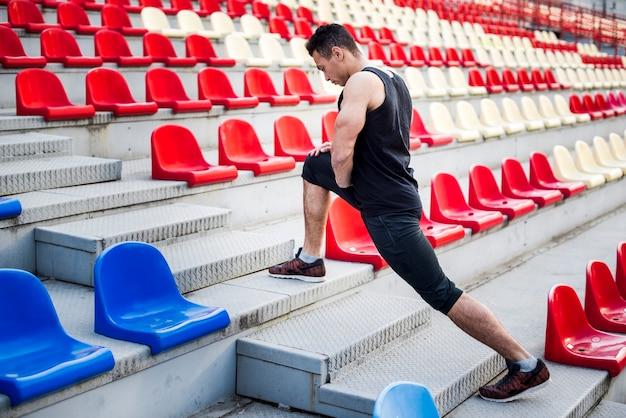 Männlicher athlet, der sein bein auf treppenhaus nahe zuschauertribünen ausdehnt Kostenlose Fotos