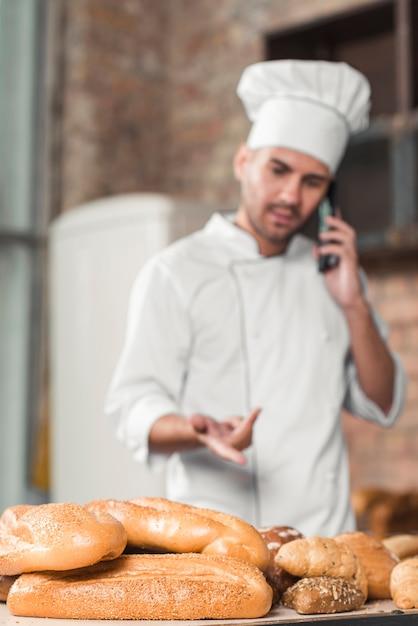 Männlicher bäcker, der auf mobiltelefon hinter dem brotlaib spricht Kostenlose Fotos