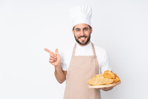 Männlicher bäcker, der einen tisch mit mehreren broten auf weißer wand hält, der finger zur seite zeigt Premium Fotos