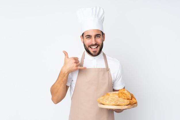 Männlicher bäcker, der einen tisch mit mehreren broten auf weißer wand hält, die telefongeste macht Premium Fotos