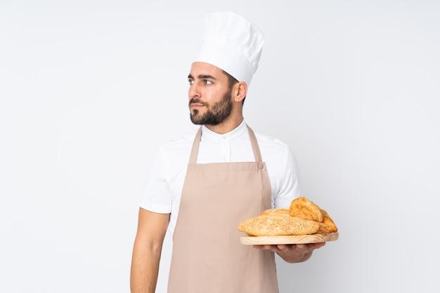 Männlicher bäcker, der einen tisch mit mehreren broten auf weißer wand schaut seite hält Premium Fotos