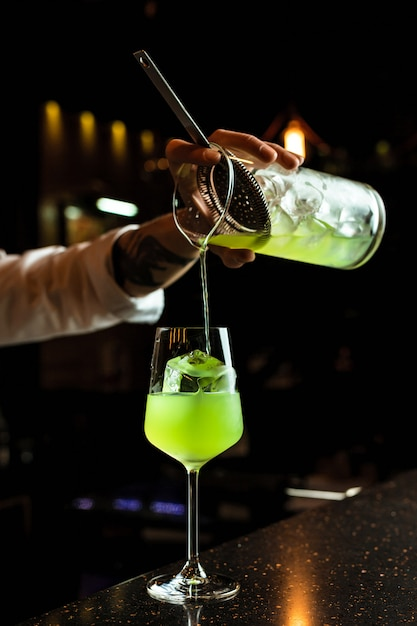 Männlicher barkeeper, der einen cocktail vorbereitet und ein grünes getränk aus einem mischglas durch ein sieb in ein weinglas mit einem eiswürfel gießt Premium Fotos