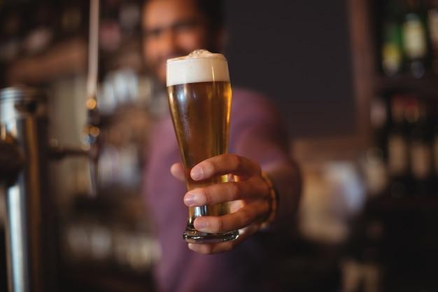 Männlicher barkeeper, der glas bier gibt Premium Fotos