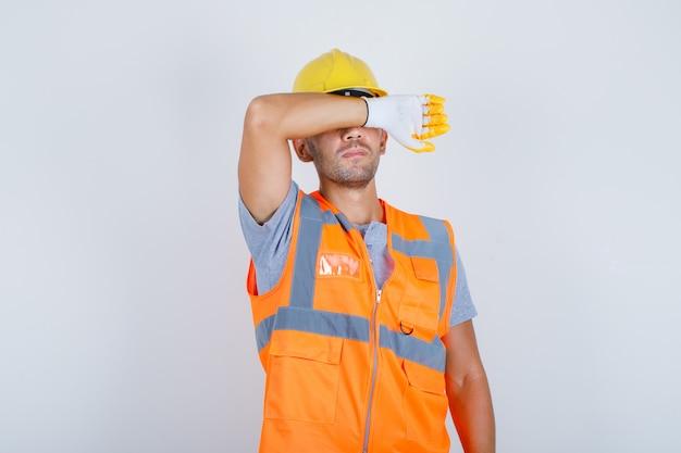 Männlicher baumeister, der augen mit arm in uniform, helm, handschuhen bedeckt und ernsthafte und traurige vorderansicht schaut. Kostenlose Fotos