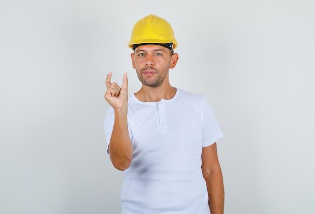 Männlicher baumeister, der kleines zeichen mit den fingern im weißen t-shirt, vorderansicht des sicherheitshelms tut. Kostenlose Fotos