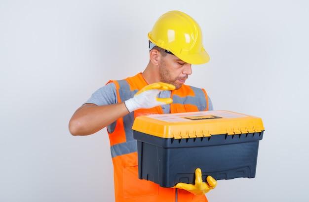Männlicher baumeister, der kunststoff-werkzeugkasten in uniform, helm, handschuhe, vorderansicht hält. Kostenlose Fotos