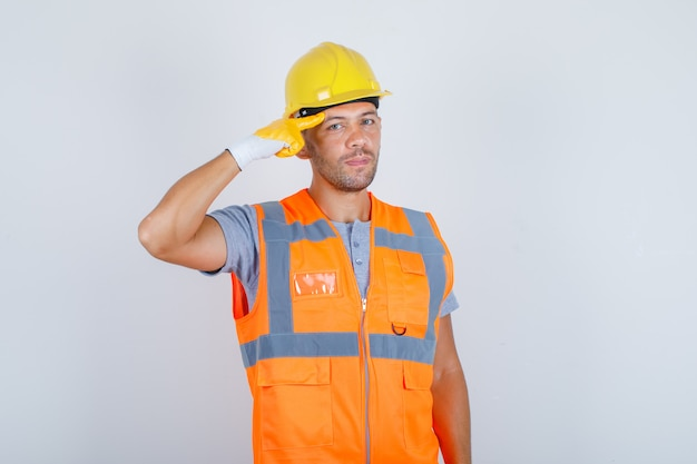 Männlicher baumeister, der mit dem finger gegen seine schläfe in der vorderansicht der uniform, des helms, der handschuhe gestikuliert. Kostenlose Fotos