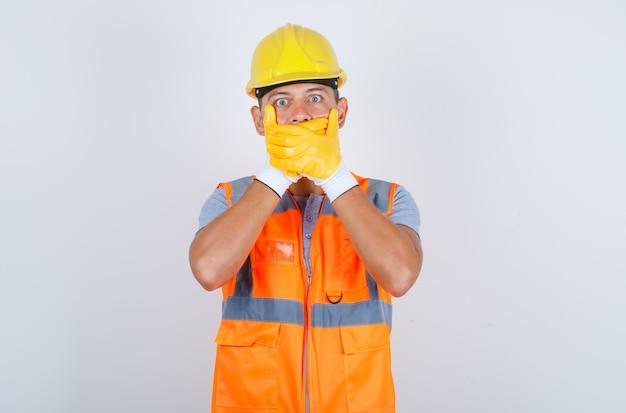 Männlicher baumeister, der mund mit händen für fehler in uniform, helm, handschuhen bedeckt und schockiert, vorderansicht schaut Kostenlose Fotos