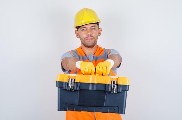 Männlicher baumeister, der werkzeugkasten hält und kamera in uniform, helm, handschuhe, vorderansicht betrachtet. Kostenlose Fotos