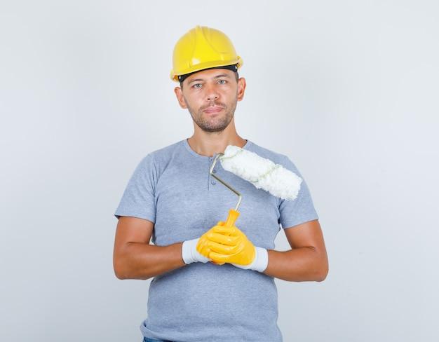 Männlicher baumeister in t-shirt, helm, handschuhen, die farbroller halten, vorderansicht. Kostenlose Fotos